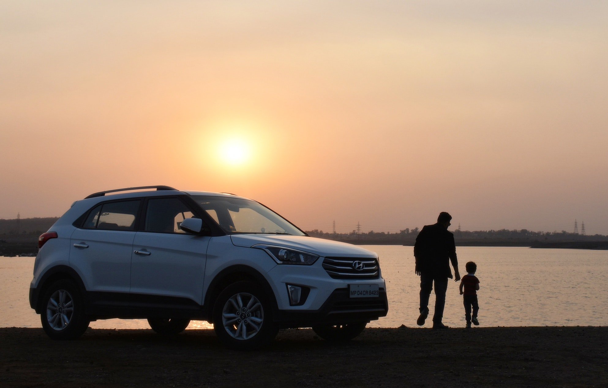 family sunset next to suv in the beach