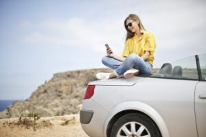 adult on car trunk in the beach looking at phone
